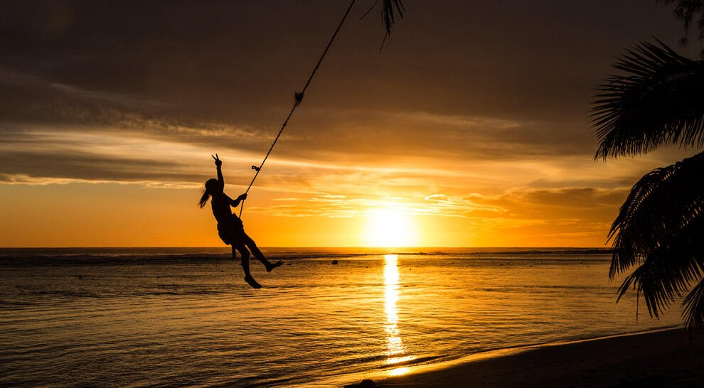 Young girl on a rope swing at sunset